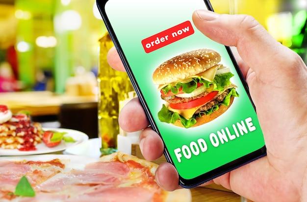 Mão segurando o telefone com pedido de aplicativo e entrega de comida sobre o fundo desfocado do restaurante