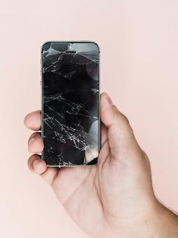 Mão segurando o telefone com tela quebrada