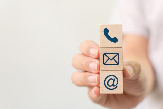 Mão segurando o telefone do símbolo do cubo de madeira do bloco, email, endereço. página do site entre em contato conosco ou conceito de marketing por e-mail
