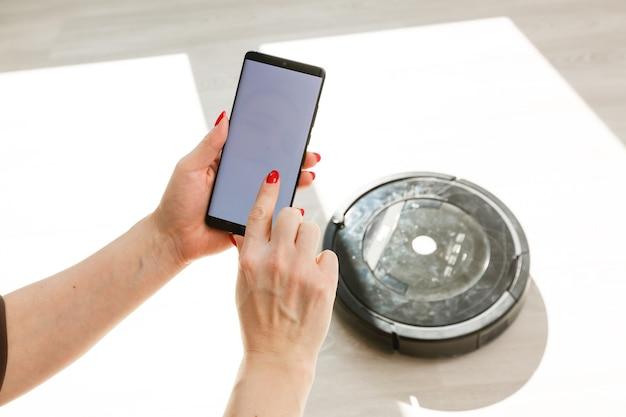 Mão segurando o telefone inteligente e o dispositivo sem fio carregado no fundo em uma sala doméstica moderna, dentro de casa. tecnologia avançada de conceito, vertical