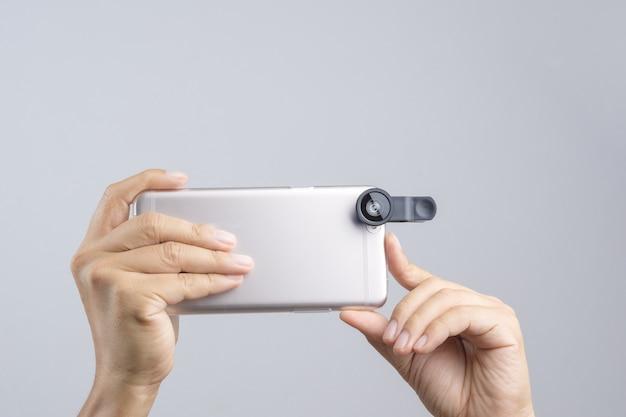 Mão segurando o telefone inteligente equipado com lente de extensão
