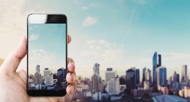 Mão segurando o telefone inteligente móvel, cidade de bangkok