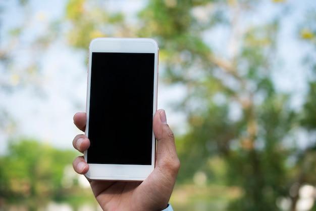 Mão segurando o telefone inteligente móvel e usando o telefone inteligente