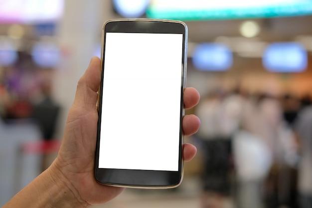 Mão segurando o telefone inteligente móvel no aeroporto