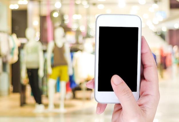 Mão segurando o telefone inteligente sobre a loja de desfoque