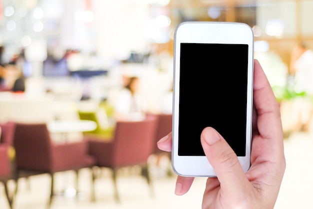 Mão segurando o telefone inteligente sobre fundo de restaurante borrão