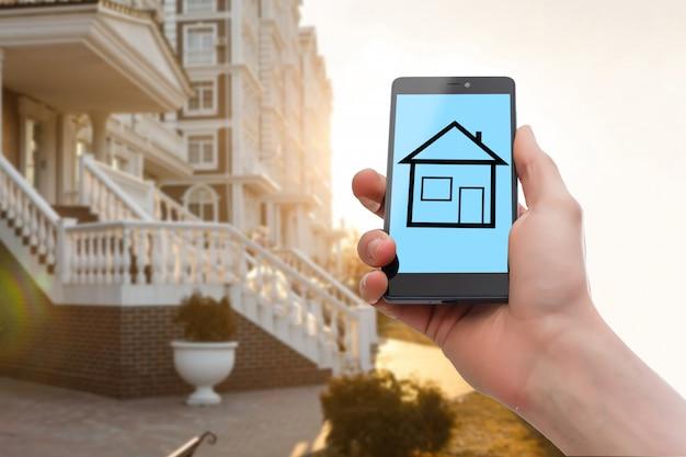 Mão segurando o telefone móvel com oferta de venda de casa