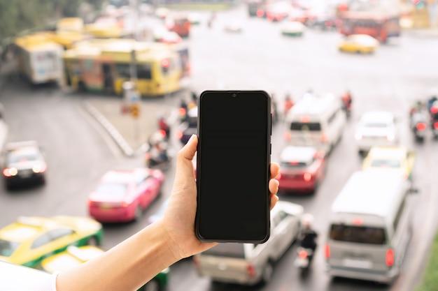 Mão segurando o telefone móvel, engarrafamento da cidade. feche e copie o espaço