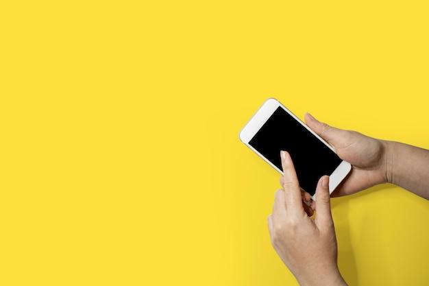 Mão segurando o telefone móvel, mão esquerda tocando a tela do telefone inteligente, isolado no fundo amarelo e traçado de recorte.