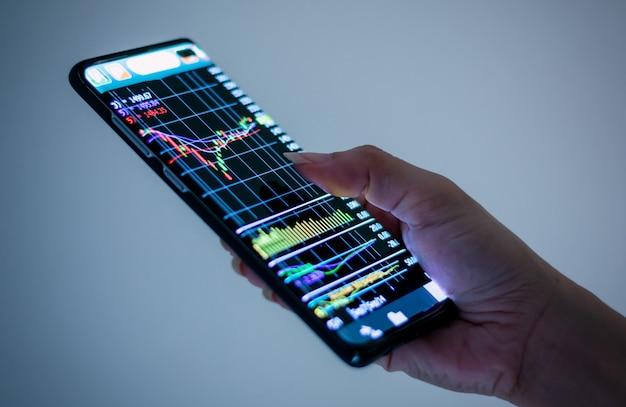 Mão segurando o telefone móvel tecnologia empresarial, gráfico, mercado financeiro e de ações