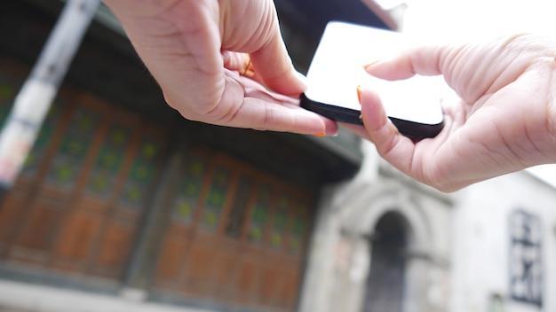 Mão segurando o telefone preto, pesquisando informações sobre fundo desfocado
