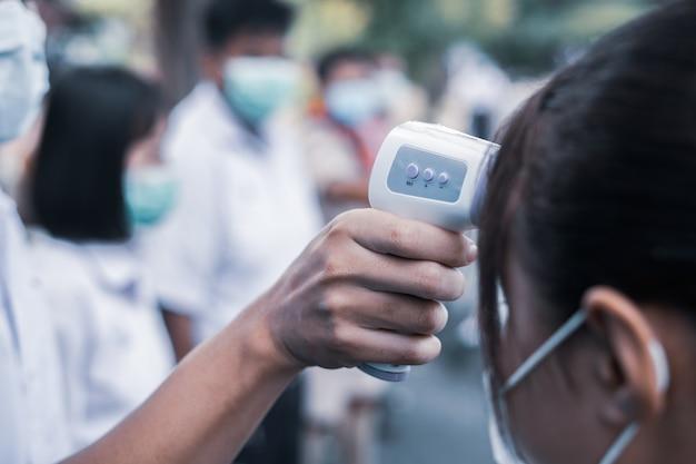 Mão segurando o teste de temperatura da testa da pistola de termômetro infravermelho para verificar o aluno
