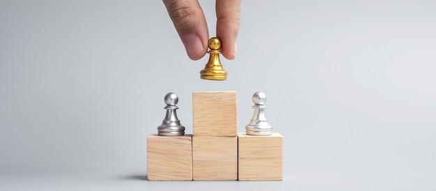 Mão segurando o topo das peças de peão de xadrez dourado