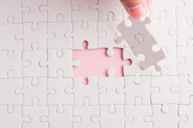 Mão segurando o último pedaço de papel branco jogo de quebra-cabeça últimas peças