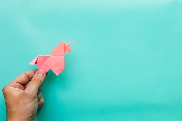 Mão segurando o unicórnio de origami rosa sobre fundo azul ciano, com espaço de cópia