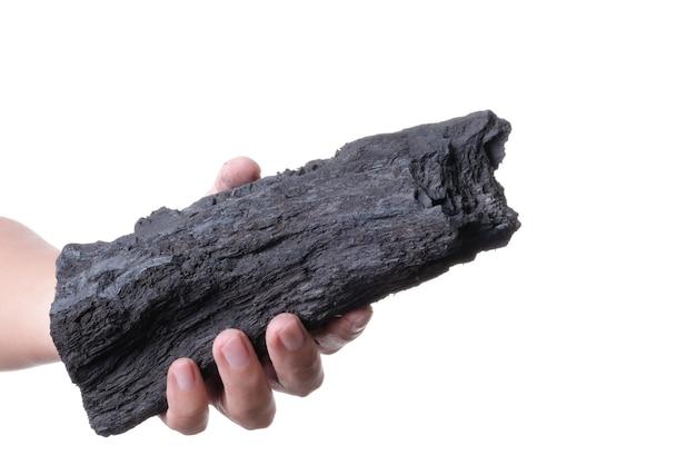 Mão segurando o uso de carvão de madeira preto natural para combustível ou absorver o mau cheiro