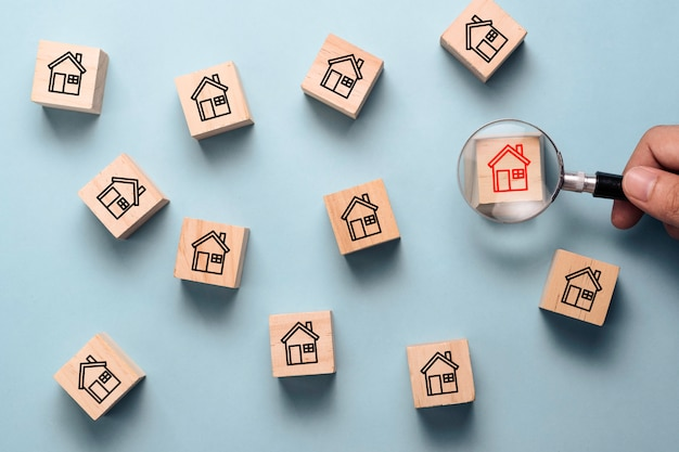 Mão segurando o vidro da lupa para procurar o ícone da casa vermelha no bloco do cubo de madeira entre o ícone da casa preta.