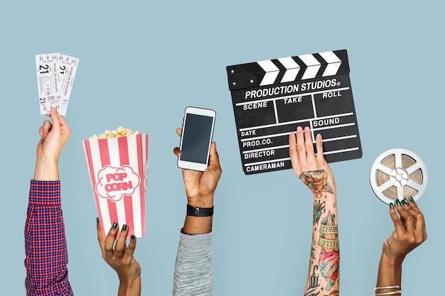 Mão segurando objetos de entretenimento isolados