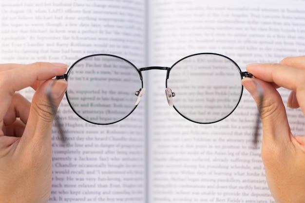 Mão, segurando, óculos, com, livro