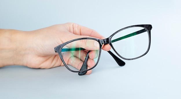 Mão segurando óculos escuros