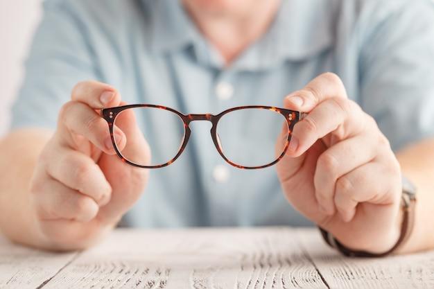 Mão segurando óculos