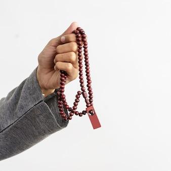 Mão segurando orando contas muçulmanas