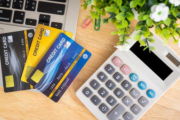 Mão segurando os cartões de crédito com um notebook e uma calculadora