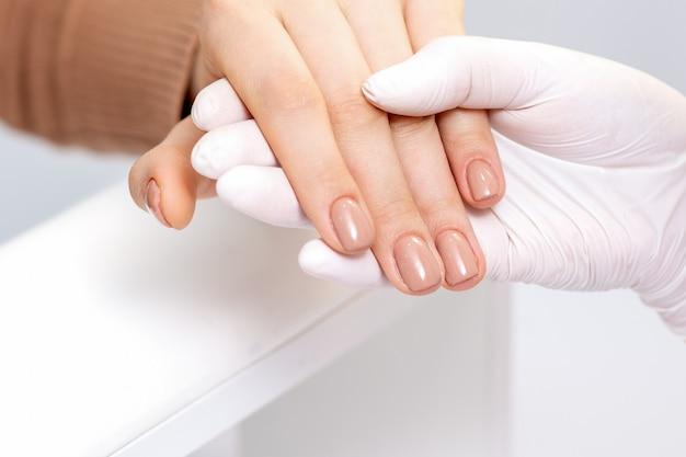 Mão segurando os dedos femininos com manicure bege