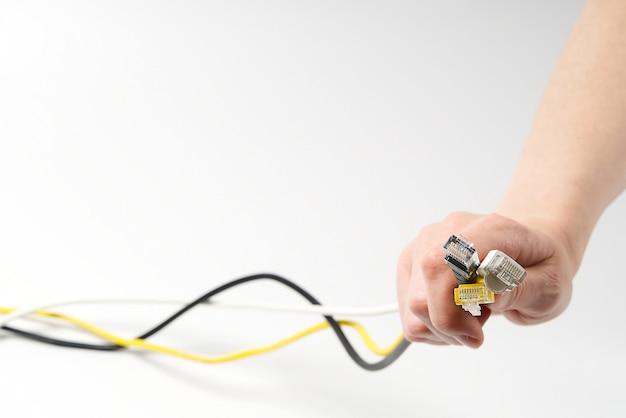 Mão segurando os fios de alta velocidade da internet no fundo branco