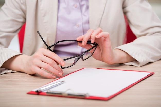 Mão segurando os óculos na mesa de trabalho