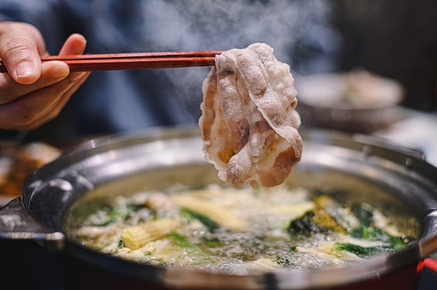 Mão segurando os pauzinhos com carne de porco kurobuta madura na panela quente de shabu shabu e sukiyaki. conceito de comida com cozinha gourmet japonesa panela quente