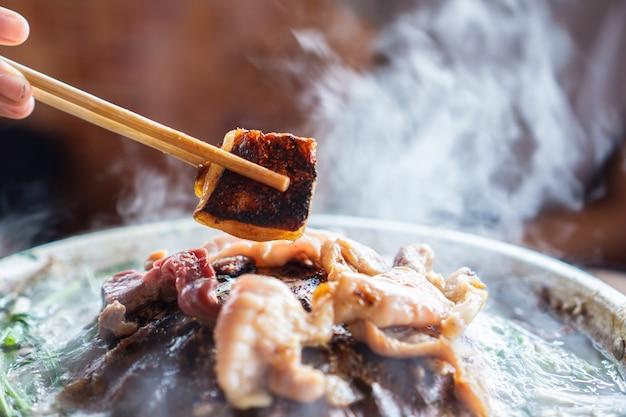 Mão segurando os pauzinhos comendo churrasco tailandês