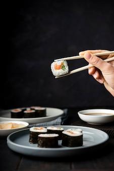 Mão segurando os pauzinhos para rolos de sushi vista frontal