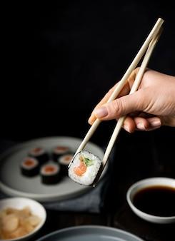 Mão segurando os pauzinhos para rolos de sushi