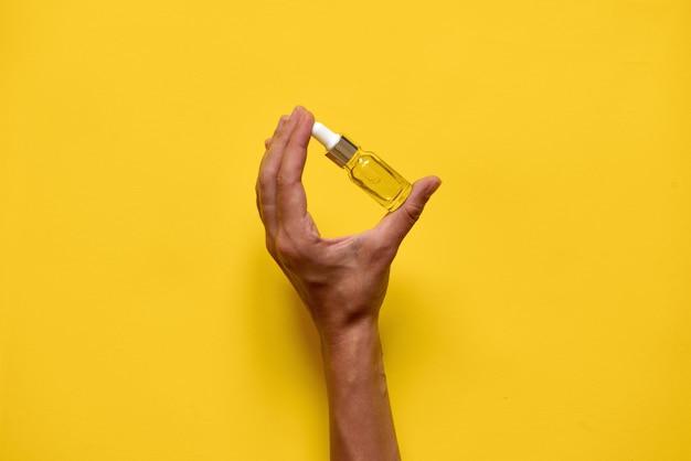 Mão segurando ottle com soro ou óleo de essência natural.