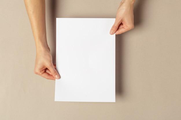 Mão segurando papéis tamanho a4
