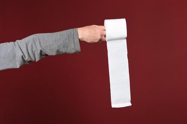 Mão segurando papel higiênico em fundo vermelho