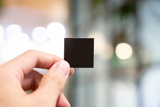 Mão segurando papel preto em branco pequeno com fundo blury