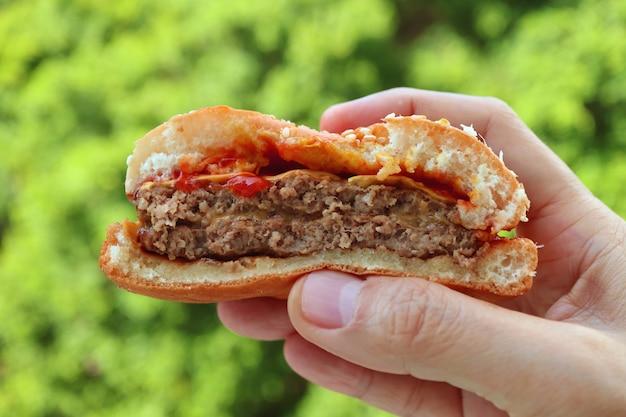 Mão segurando parcelada ao meio hambúrguer com folhagem verde embaçada