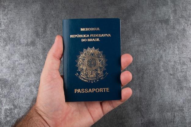 Mão segurando passaporte brasileiro com fundo cinza