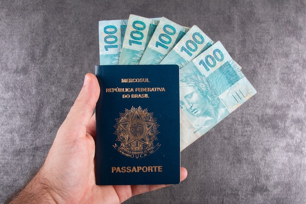 Mão segurando passaporte brasileiro com notas de cem reais.