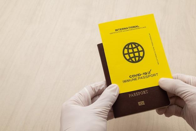 Mão segurando passaportes de vacina como prova de que o titular foi vacinado contra covid-19, requisito para viagens internacionais.