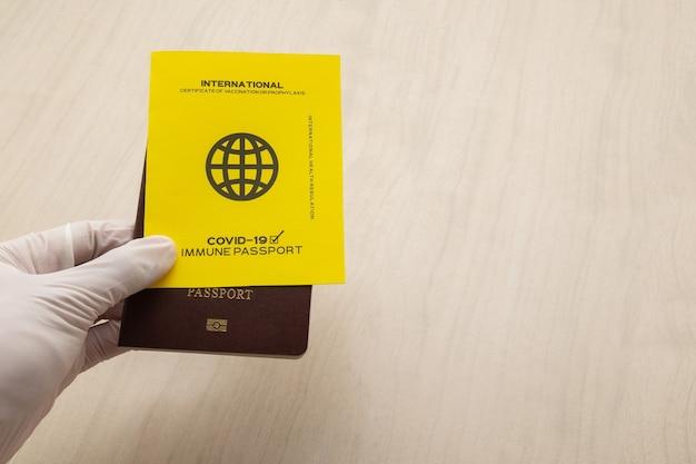 Mão segurando passaportes de vacina como prova de que o titular foi vacinado contra covid 19