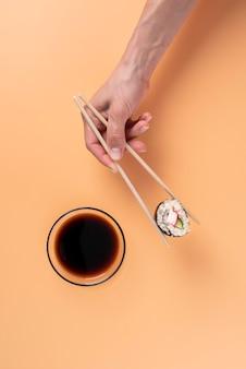 Mão segurando pauzinhos comida asiática