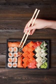 Mão segurando pauzinhos e pegando sushi