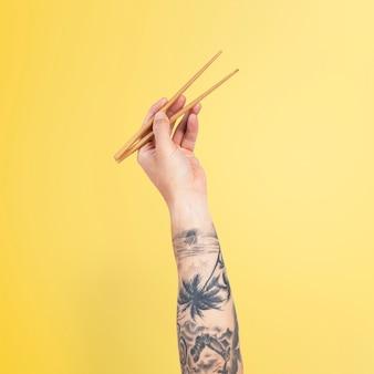 Mão segurando pauzinhos para o conceito de comida