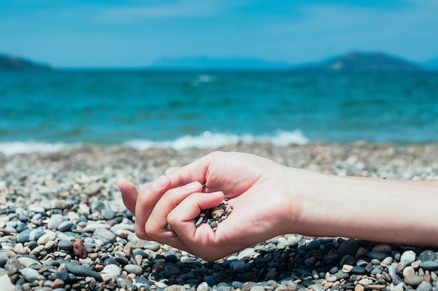 Mão segurando pedras em uma praia, água do mar turquesa no fundo