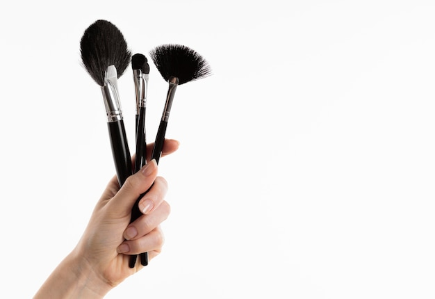 Mão segurando pincéis de maquiagem com espaço de cópia
