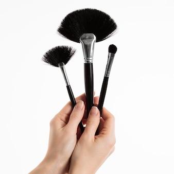 Mão segurando pincéis de maquiagem