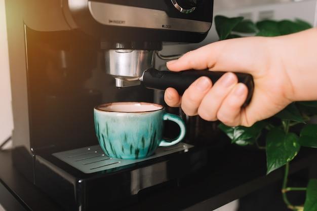 Mão segurando porta-filtro, xícara de café verde na cafeteira, hora do café
